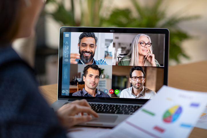 Back view of business woman talking to her colleagues about business plan in video conference. Multiethnic business team using laptop for a online meeting in video call. Group of buinessmen and businesswomen smart working from home. (Back view of busi